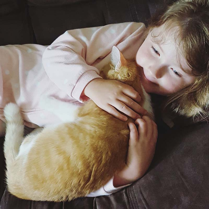 Image of a girl cuddling with her cat